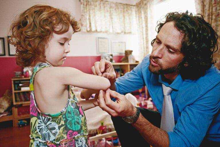 Dad putting bandaid on child's arm