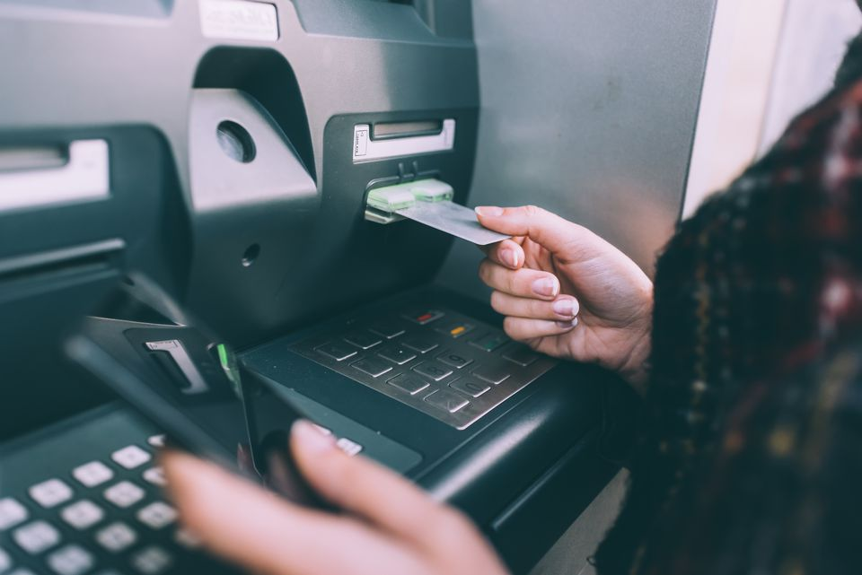 Hand of young woman inserting credit card into cash machine