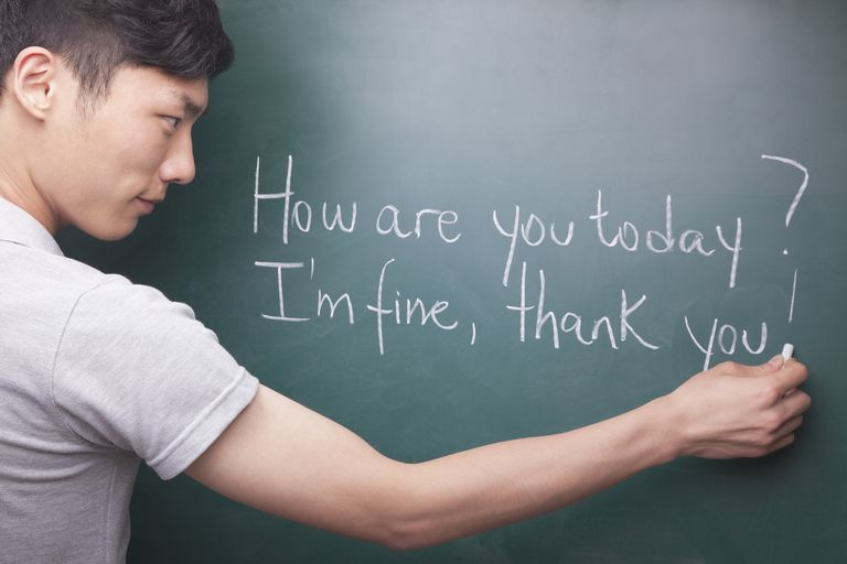 Young man writing English sentences on the blackboard