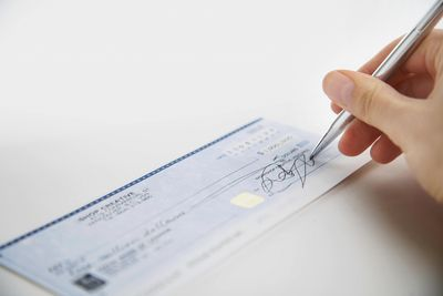 See how to write dollars and cents on a check female hand signing check ccuart Gallery