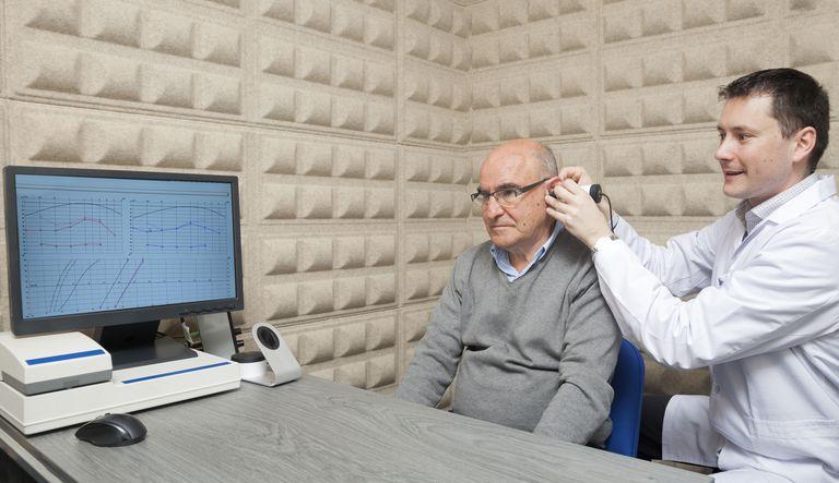 Audiologist testing man