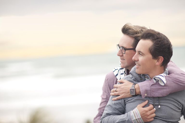 Gay couple hugging on beach