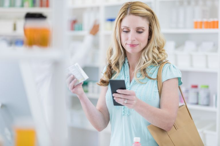 Woman uses smart phone while in pharmacy