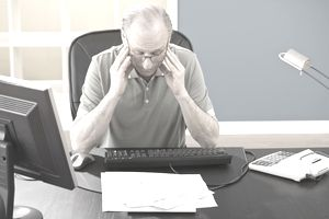 Tired man at desk with paperwork