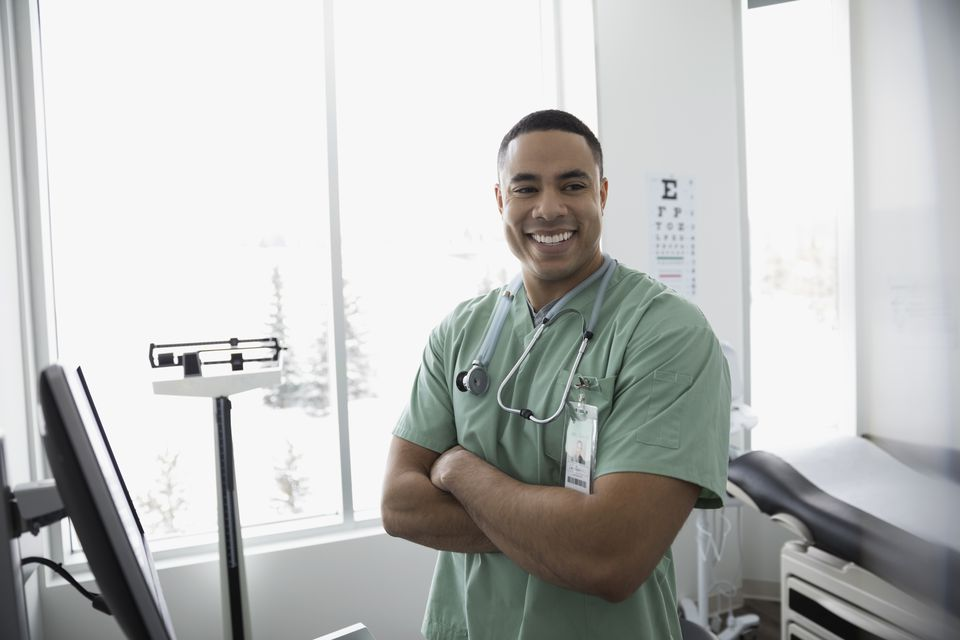 Portrait happy male nurse with arms crossed in clinic examination room