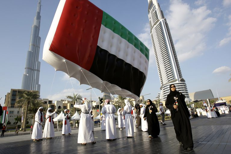 Emirati men and women carry UAE flag in front of Burj Khalifa during UAE National Day, Dubai, UAE.