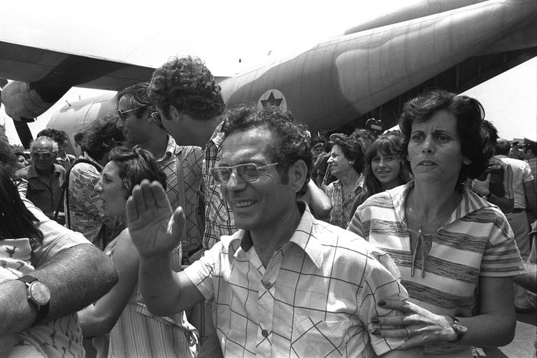 A joyous wave of the hand and a tense searching look by homecoming Air France hostages, who were rescued from Entebbe Airport.