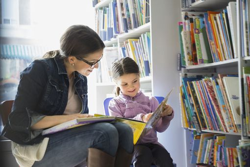 Mother and daughter reading book in bookstore