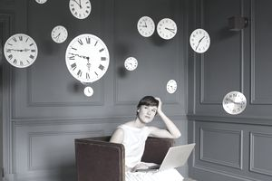 Woman on laptop surrounded by clocks