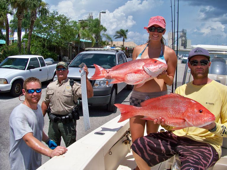 A couple showing off their catch of red snapper