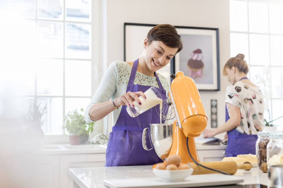 Female caterer baking, using stand mixer in kitchen