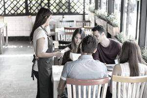 Waitress serving a group of friends at a restaurant