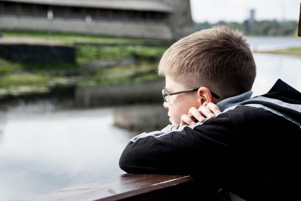 boy leaning on bridge looking at water