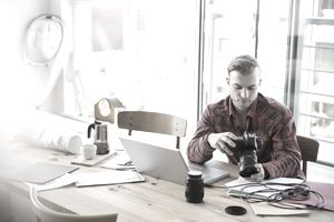 Photographer with camera uploading to laptop at table