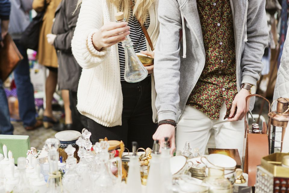 young couple looking at glassware at yard sale