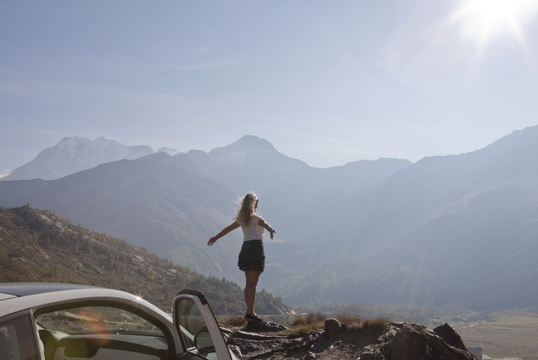 woman with arms outstretched on edge of cliff
