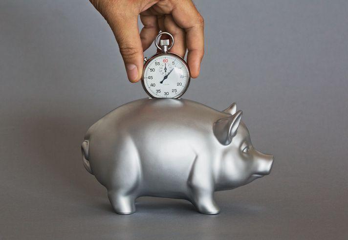 time saving photo illustration depositing stopwatch into piggy bank