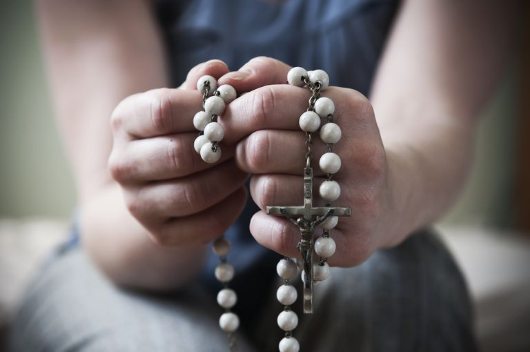 Close-up of young woman using prayer beads