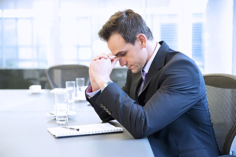 Businessman with head in hands in conference room