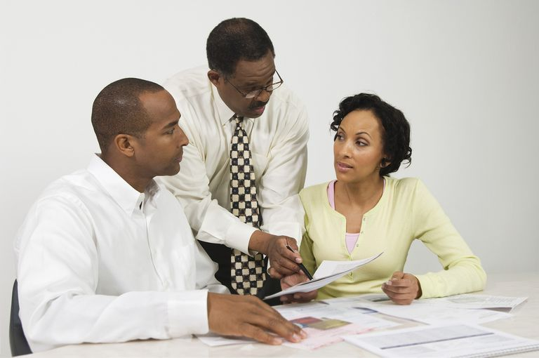 Man and woman talking over paperwork with advisor