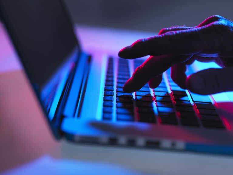 A moodily-lit hand typing on a laptop keyboard.