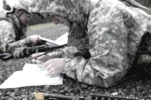 Army soldiers plot eight-digit grid coordinates on a map before participating in a daytime land navigation course while competing for the Expert Field Medical Badge at Joint Base Lewis-McChord, Wash