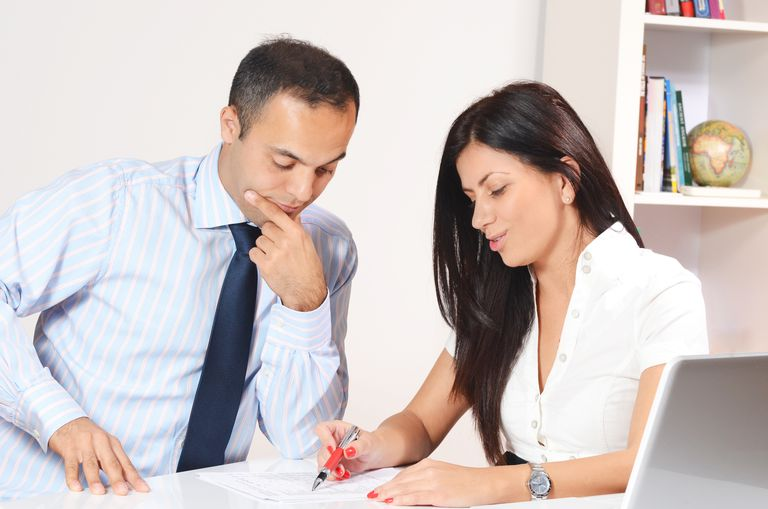 two business people looking at financial report