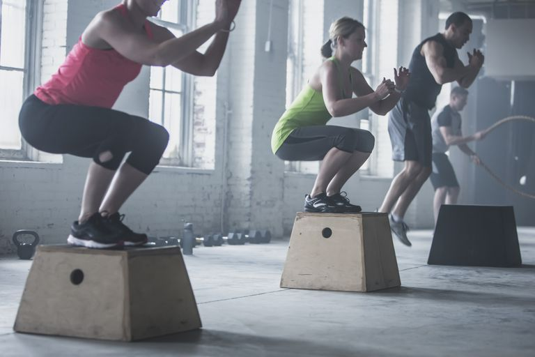 men and women doing box jumps in Crossfit gym