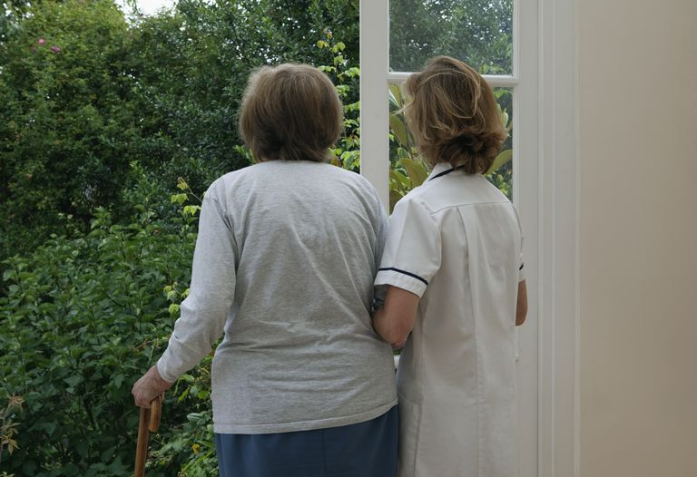 Nurse supporting elderly woman