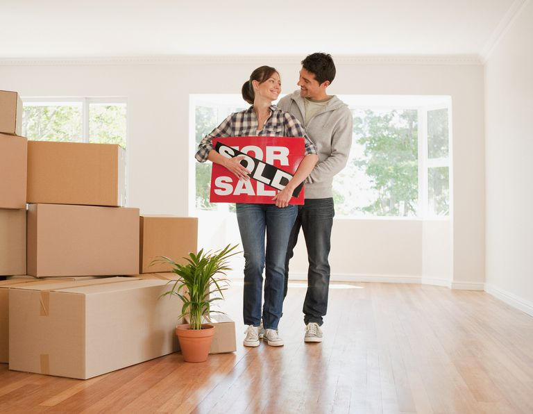 couple with sold sign in living room next to boxes