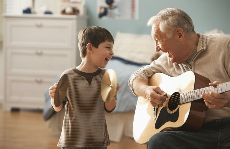 grandfather with boy playing guitar