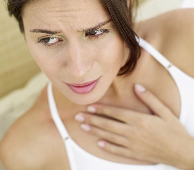 woman with a sore throat wondering if it is a symptom of esophageal cancer