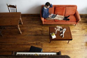 Musician Relaxing on Living Room Couch with Laptop