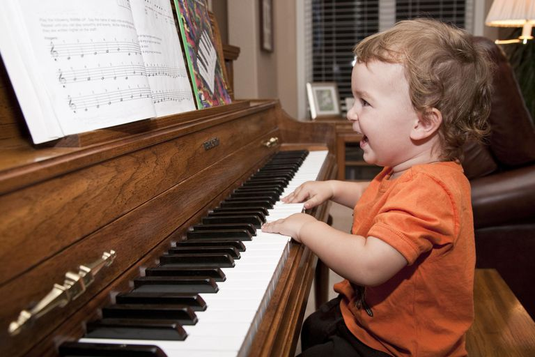 A toddler happily playing piano.