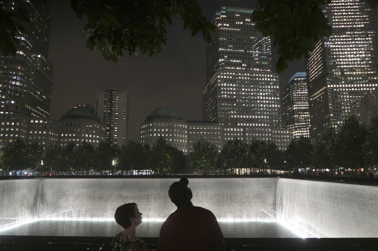 Night view of two people looking up at skyscrapers over the 911 National Memorial reflecting pool
