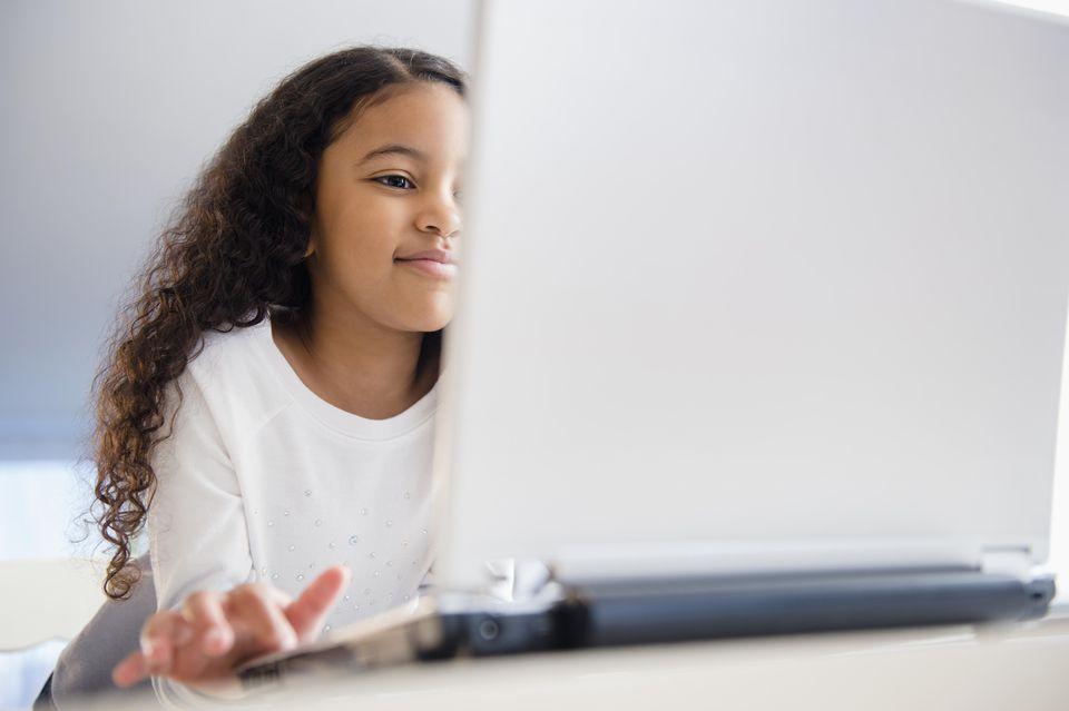Close up of mixed race girl using laptop