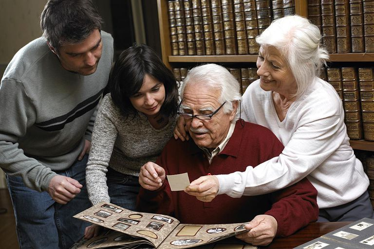 Family looking at photo album together, smiling