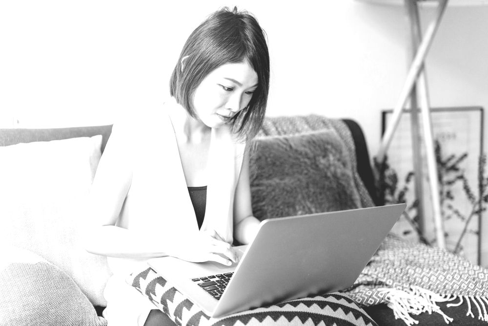 Woman writing letter on couch at home