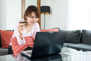 Young woman sitting on couch shopping online at home