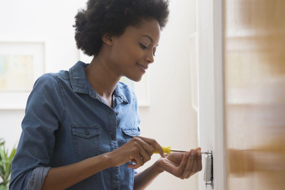 Woman fixing light switch