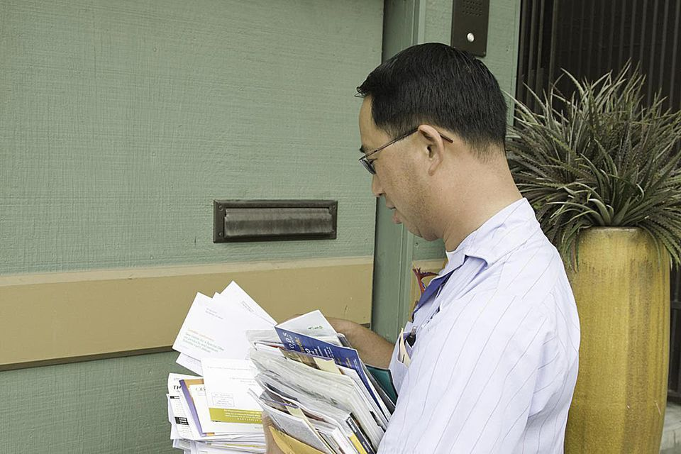 Postman with pile of letters standing outside house