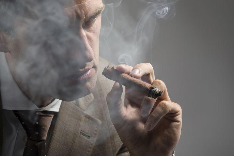 man smoking cigar with secondhand smoke around him