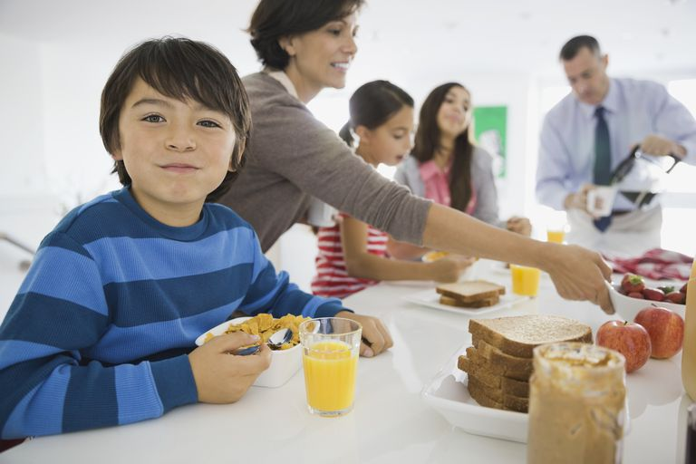 9 year old child emotional development - boy smiling with family at breakfast