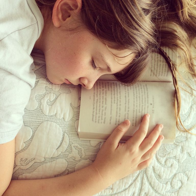A tired young girl who fell asleep while reading a book.