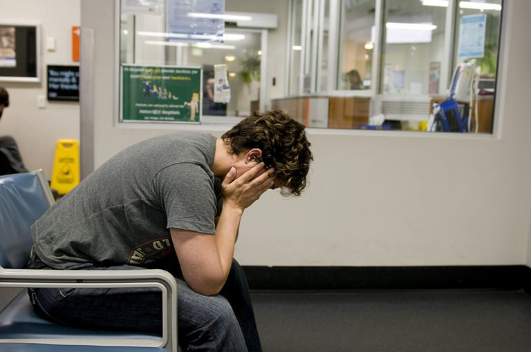 man holding his head in pain in a waiting room