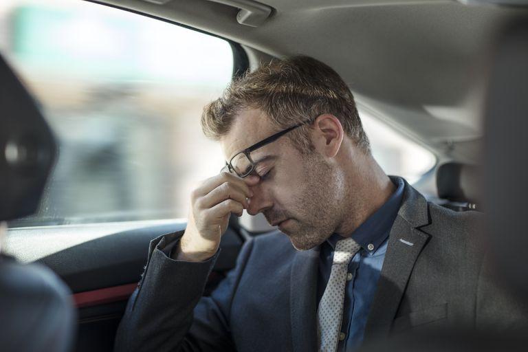 Businessman sitting in back of car, rubbing weary eyes