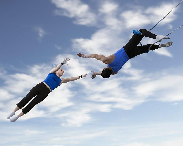 Man and woman on trapeze reaching for each other