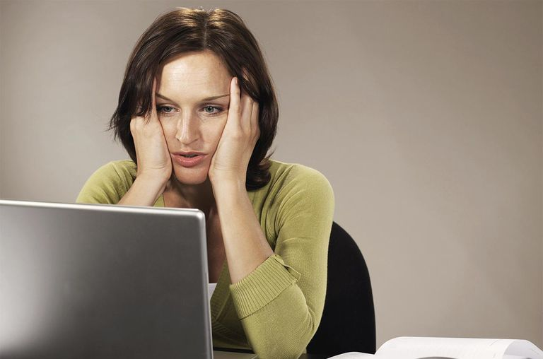 Woman sitting at laptop, elbows on desk, holding head in hands