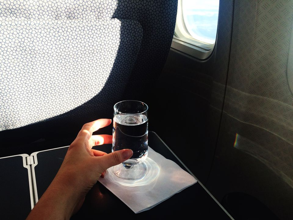 Cropped Hand Reaching For Drinking Glass By Airplane Window