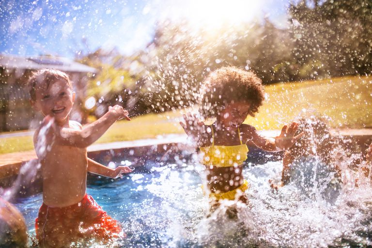 Little girl and friend splashing water in swimming pool